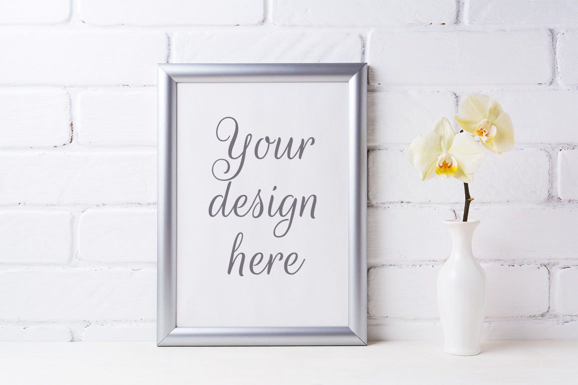 Print on Demand: Silver Frame Mockup with Soft Yellow Orchid in Vase Graphic Product Mockups By TasiPas