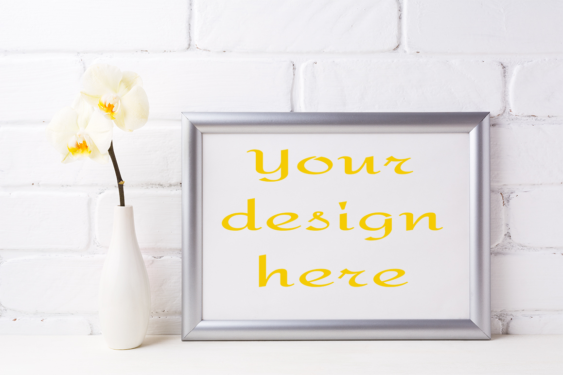 Print on Demand: Silver Landscape Frame Mockup with Soft Yellow Orchid in Vase Graphic Product Mockups By TasiPas
