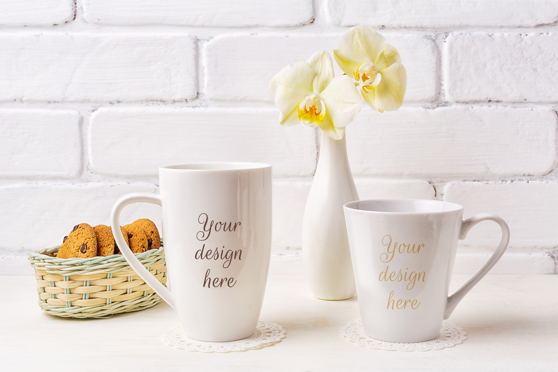 Print on Demand: Two White Coffee Latte and Cappuccino Mug Mockup with Soft Yellow Orchid in Vase and Cookies in Wicker Basket Graphic Product Mockups By TasiPas