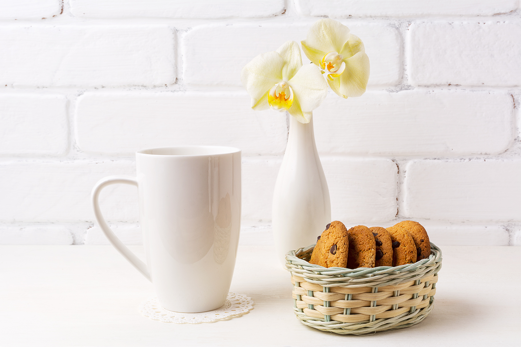 Download Free White Coffee Cappuccino Mug Mockup With Soft Yellow Orchid In Vase for Cricut Explore, Silhouette and other cutting machines.