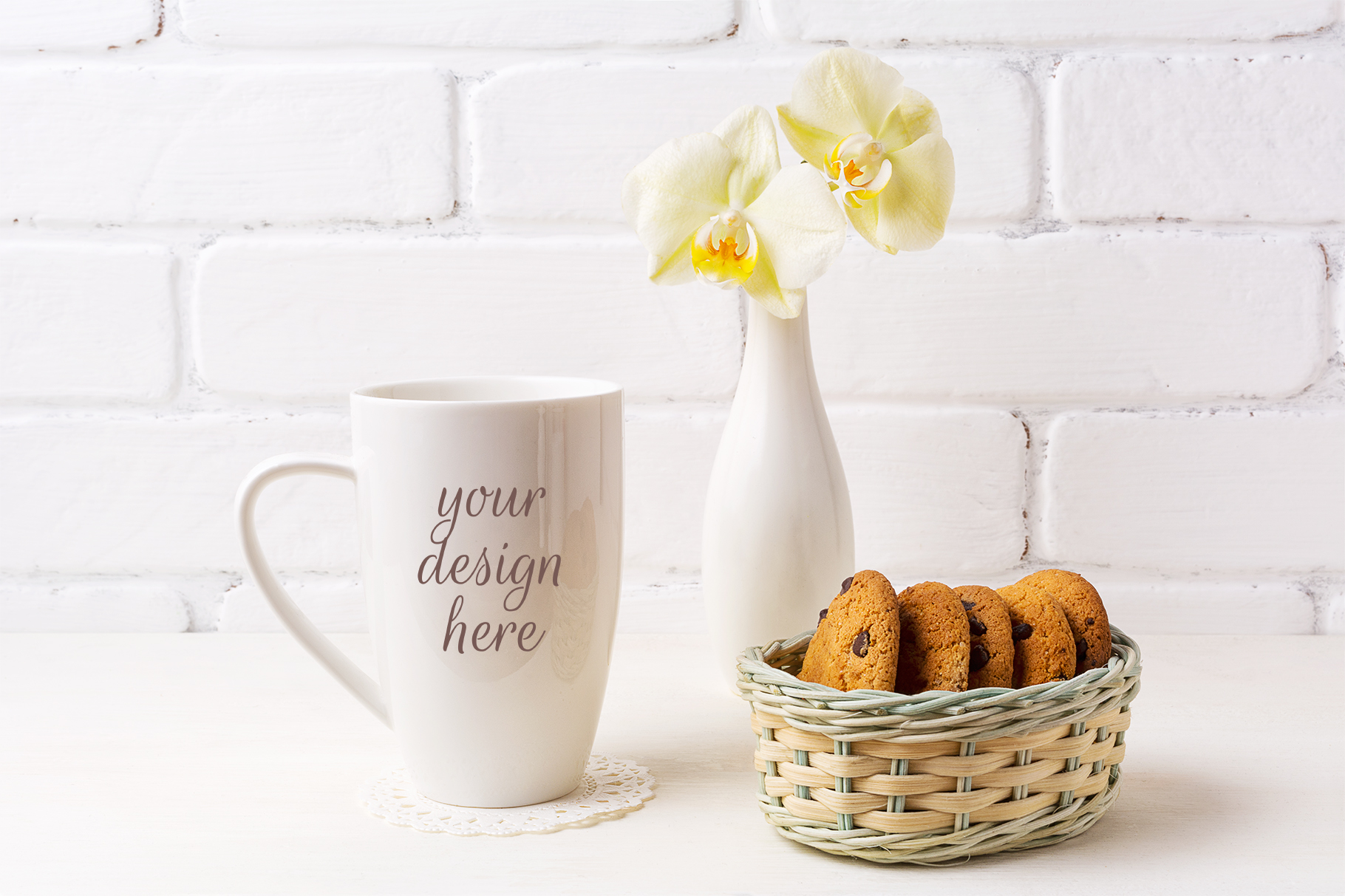 Print on Demand: White Coffee Cappuccino Mug Mockup with Soft Yellow Orchid in Vase and Cookies in Wicker Basket Graphic Product Mockups By TasiPas