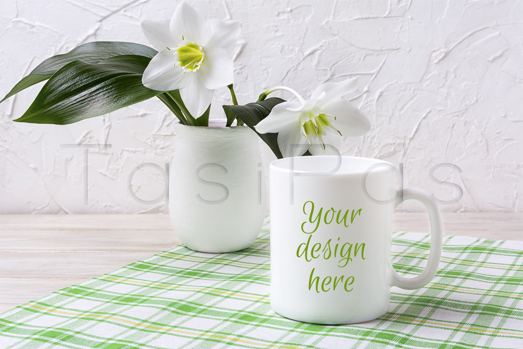 Print on Demand: White Mug Mockup with Lily in Vase on Green Checkered Napkin Graphic Product Mockups By TasiPas