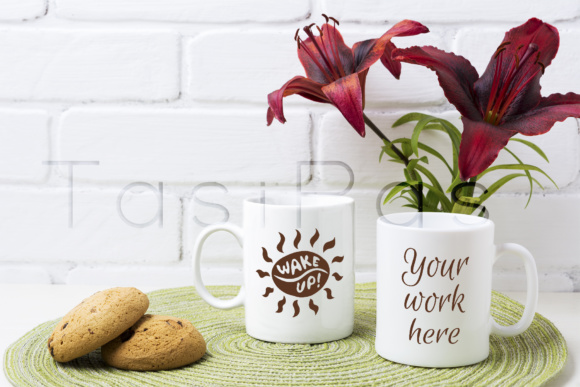 Print on Demand: Two Coffee Mug Mockup with Red Lily and Cookie Grafik Produktmodelle von TasiPas