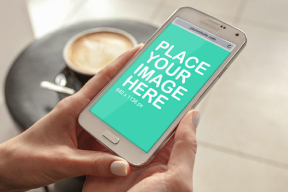 Print on Demand: Smart Phone in Hand Graphic Product Mockups By Outflow Designs