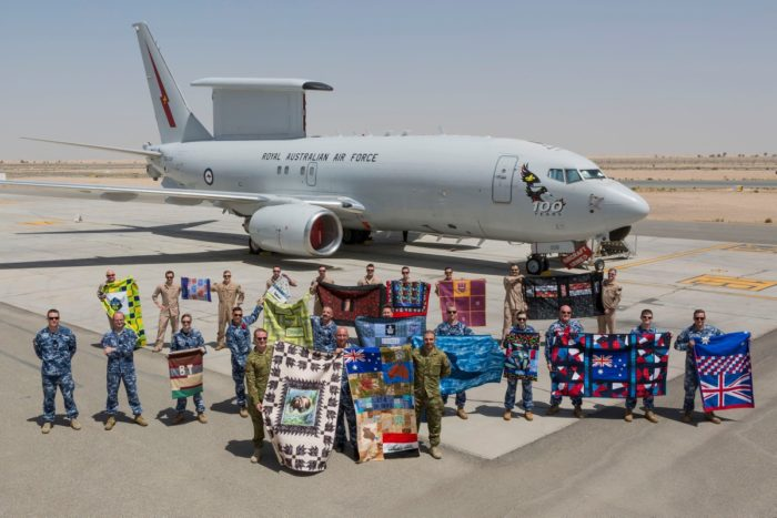 military persons holding quilts in desert with grey plane