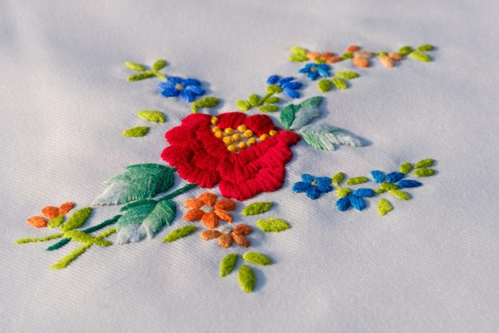 machine embroidered red rose with floral outline