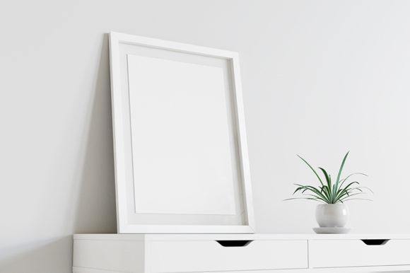 Download Free Framed Poster Mockup On White Table Graphic By Muhazdinata for Cricut Explore, Silhouette and other cutting machines.
