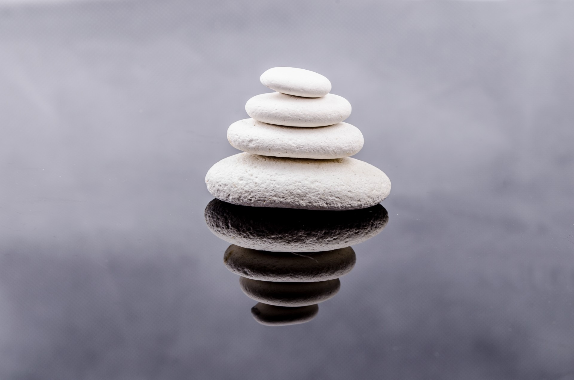 A balanced design of stacks of rocks with different colours and a contrasting background